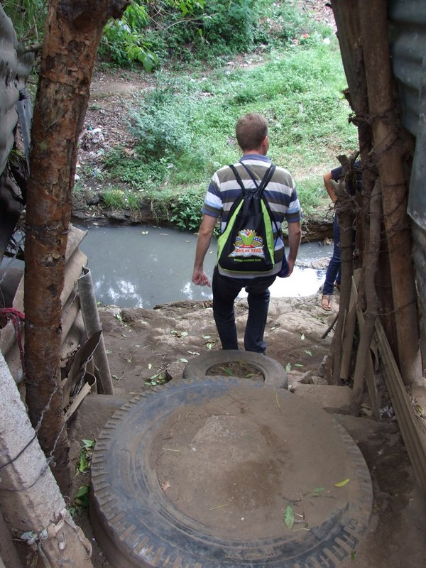 "Nathan walking down their steps to leave - this is the ""stream"" of sewage the children jump every day to get to school and it's low now"