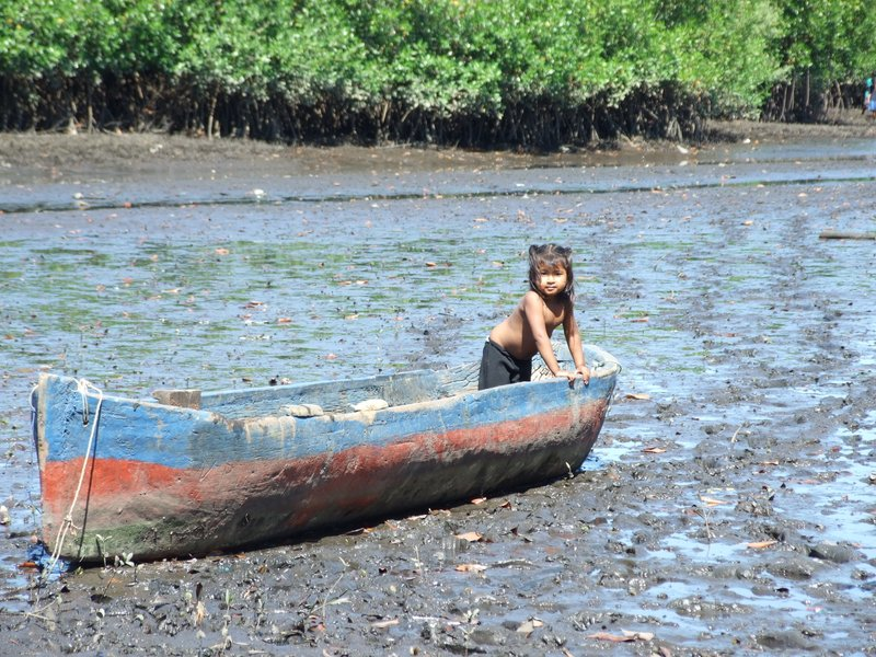 The neighbor girl playing in a boat on the mud flats waiting for the boys to return